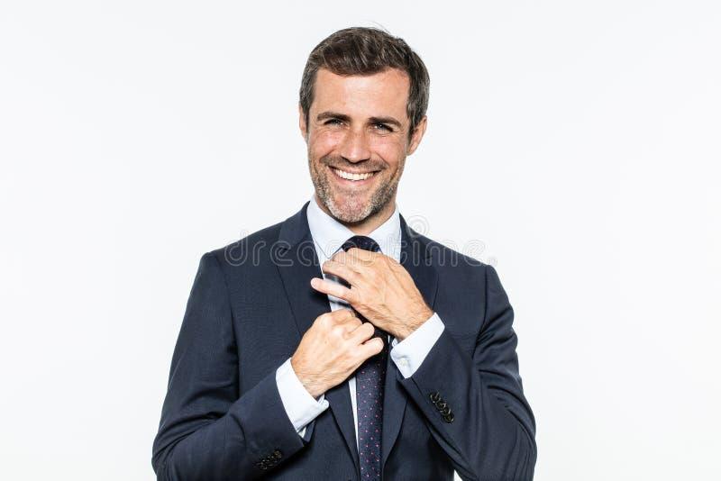 Homme d'affaires barbu heureux fixant son lien élégant avec le noeud élégant images libres de droits