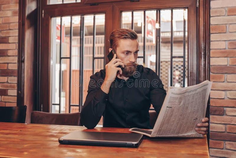 Homme d'affaires barbu lisant un journal photographie stock libre de droits