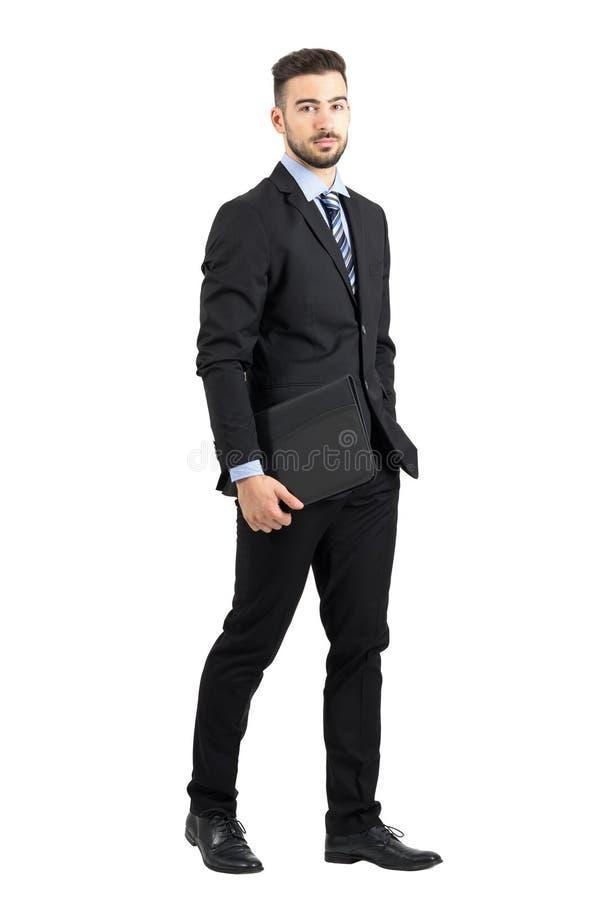 Homme d'affaires barbu sûr sérieux tenant le dossier de document marchant tout en regardant l'appareil-photo photos libres de droits