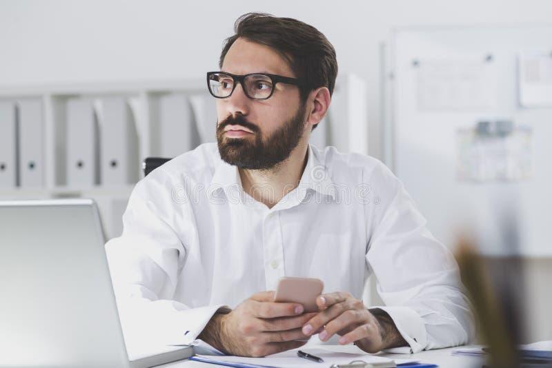 Homme d'affaires barbu tenant le téléphone intelligent images stock