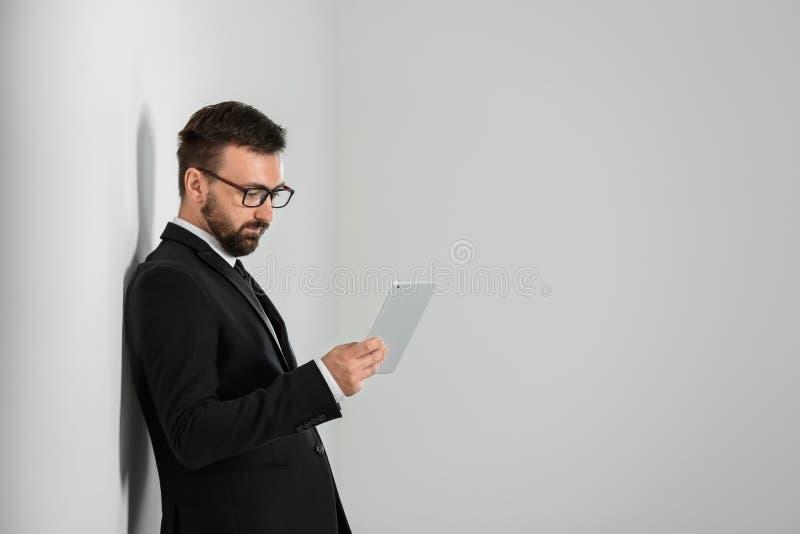 Homme d'affaires bel avec la tablette à l'intérieur image stock