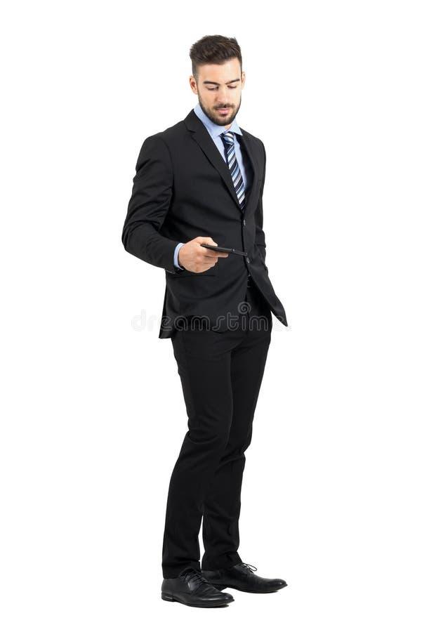 Homme d'affaires bel ayant à téléphone portable du sien la vue de côté de poche images libres de droits