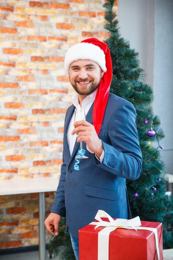 Homme d'affaires bel dans un chapeau de Santa avec un verre sur un fond de fête Concept de fête de Noël d'affaires photo libre de droits