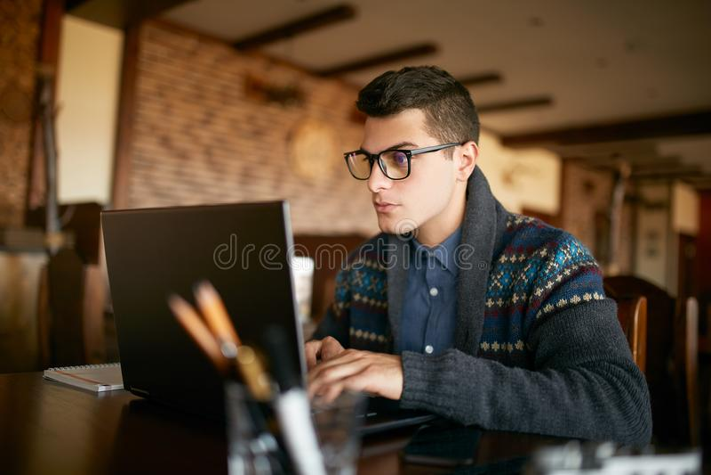 Homme d'affaires bel d'indépendant dans les verres et le chandail d'hiver travaillant diligemment sur l'ordinateur portable en ca photographie stock
