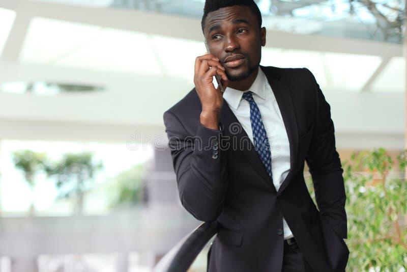 Homme d'affaires bel réussi d'afro-américain parlant au téléphone portable dans le bureau moderne photo libre de droits