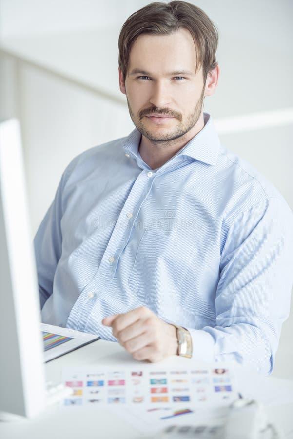 Homme d'affaires bel s'asseyant au bureau photos libres de droits