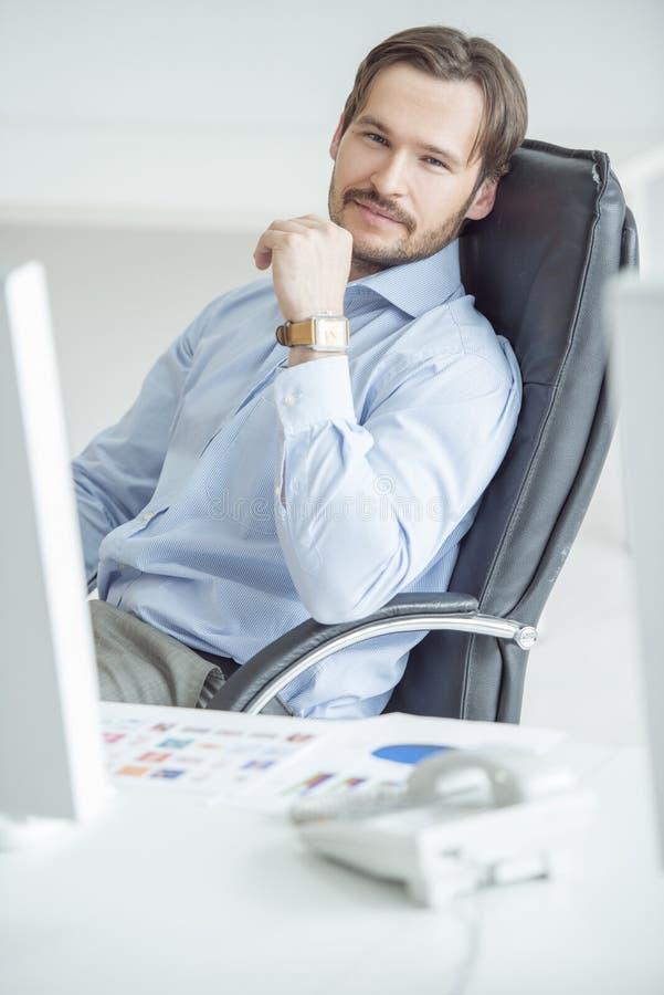 Homme d'affaires bel s'asseyant dans la chaise devant l'ordinateur photographie stock