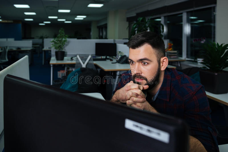 Homme d'affaires bel s'asseyant sur le lieu de travail et travaillant tard photo libre de droits