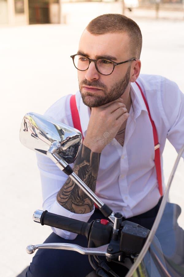 Homme d'affaires bel s'asseyant sur une motocyclette regardant loin images libres de droits