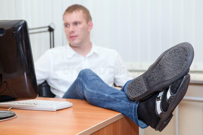 Homme d'affaires bel se reposant avec des pieds sur le bureau photos libres de droits