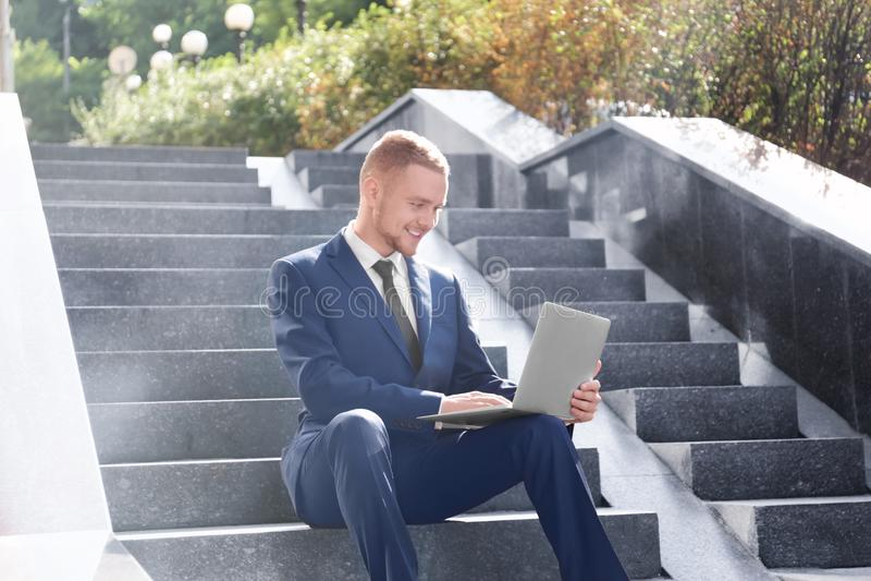 Homme d'affaires bel travaillant avec l'ordinateur portable tout en se reposant sur des escaliers dehors photos stock