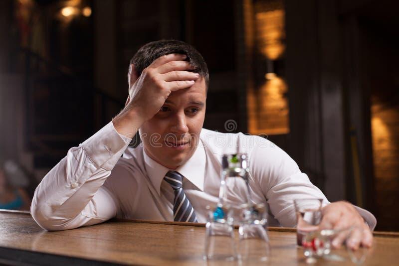 Homme d'affaires bouleversé ayant la boisson dans la barre photo stock