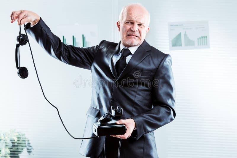 Homme d'affaires bouleversé tenant un téléphone à la longueur de bras photo stock