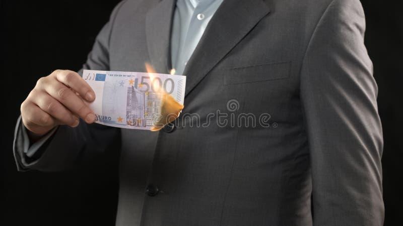 Homme d'affaires brûlant la facture de l'euro cinq cents, argent gaspillant le concept de faillite photos libres de droits