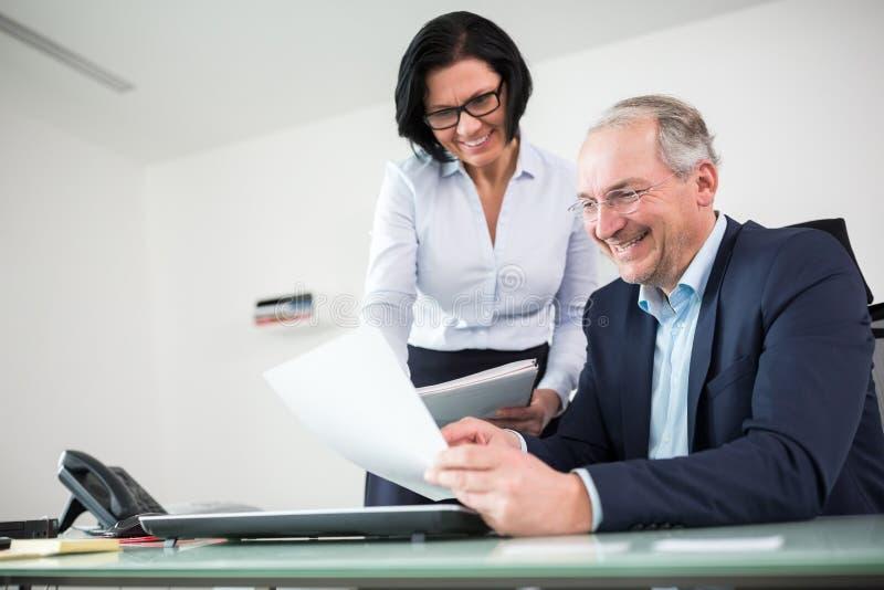 Homme d'affaires And Businesswoman Discussing au-dessus du document dans le bureau photos stock