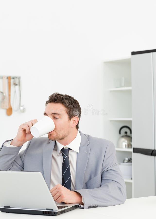Homme d'affaires buvant tandis qu'il regarde sa La photo libre de droits