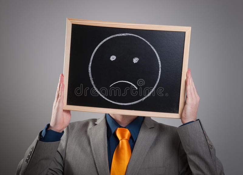 Homme d'affaires cachant son visage avec un panneau d'affichage blanc avec un fa triste photo libre de droits