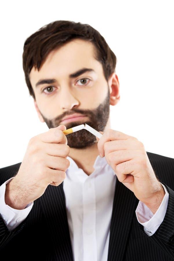 Homme d'affaires cassant une cigarette photos libres de droits