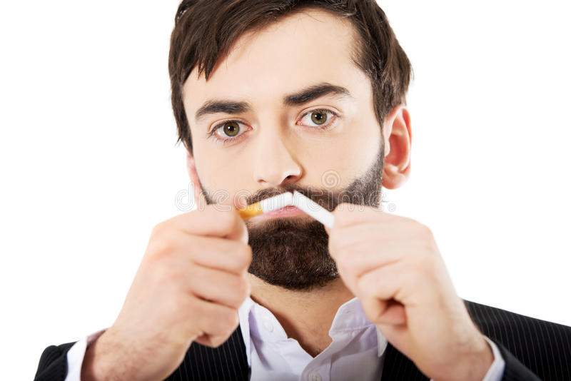 Homme d'affaires cassant une cigarette images libres de droits