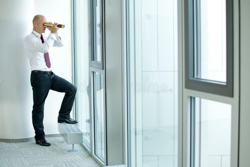 homme d'affaires caucasien remarquant utilisant le télescope par la fenêtre de bureau image stock