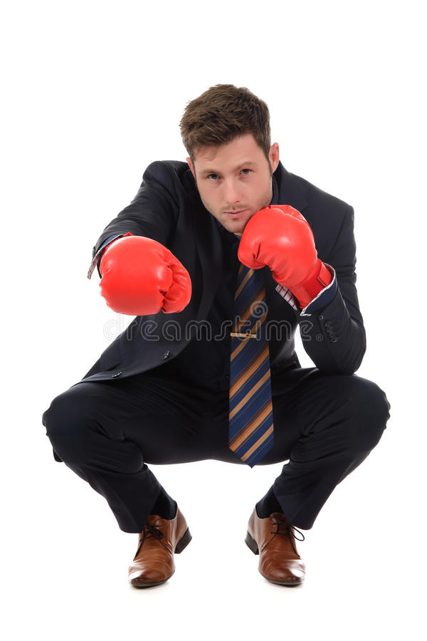Homme d'affaires caucasien s'accroupissant, gants de boxe photos stock