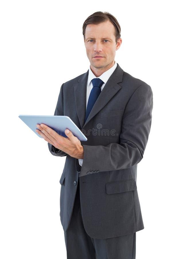 Homme d'affaires charismatique sérieux tenant un ordinateur de comprimé photos libres de droits