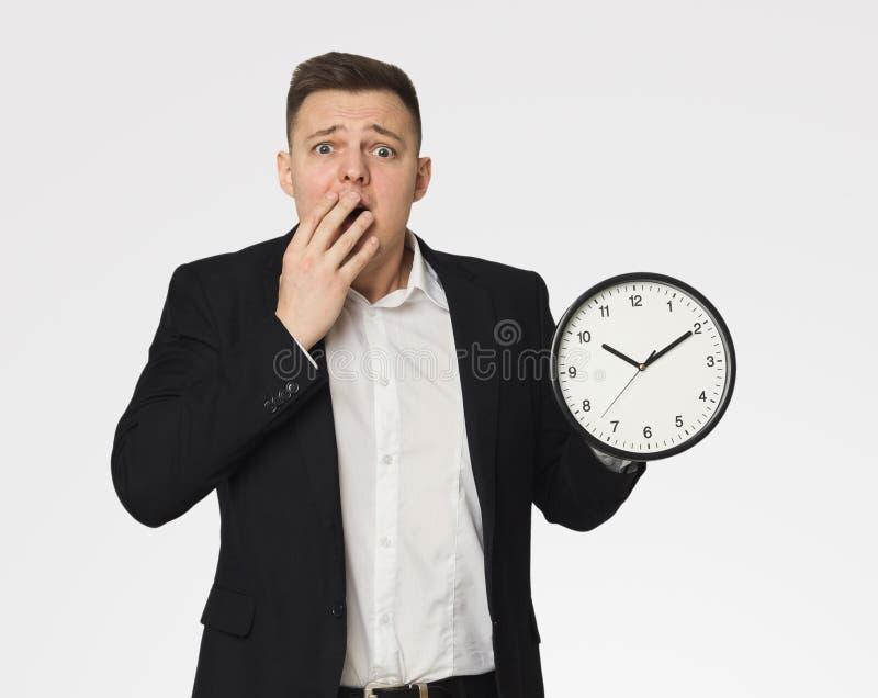 Homme d'affaires choqué tenant l'horloge images libres de droits