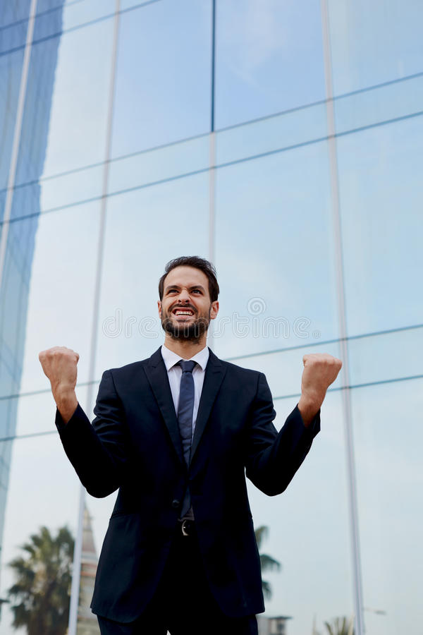 Homme d'affaires comblé soulevant ses bras dans la victoire en dehors d'un immeuble de bureaux photographie stock libre de droits