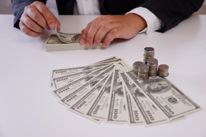 Homme d'affaires comptant l'argent avec des pièces de monnaie et l'argent au-dessus du bureau photographie stock