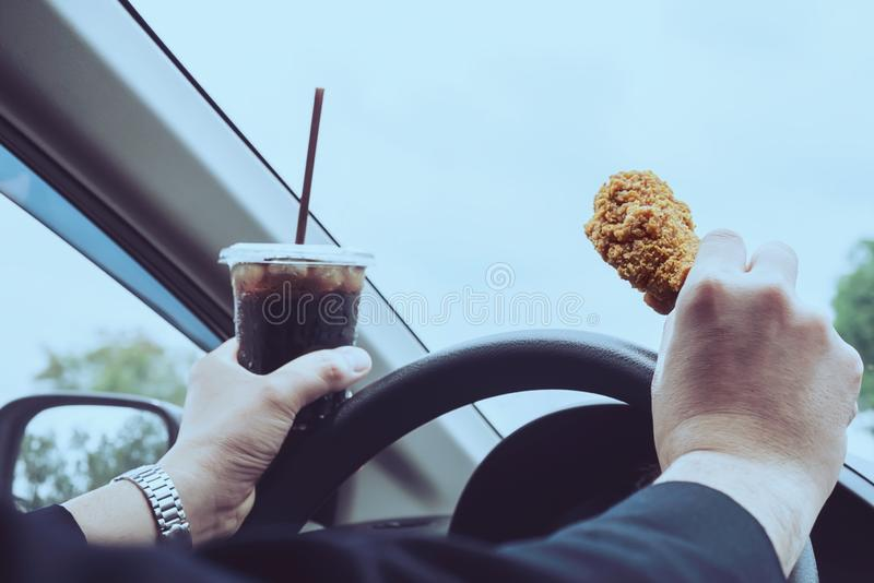 Homme d'affaires conduisant la voiture tout en mangeant le poulet frit et la boisson non alcoolisée froide photographie stock
