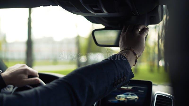 Homme d'affaires conduisant une voiture et regardant dans le miroir de vue arrière barre Homme d'affaires dans la voiture regarda image stock
