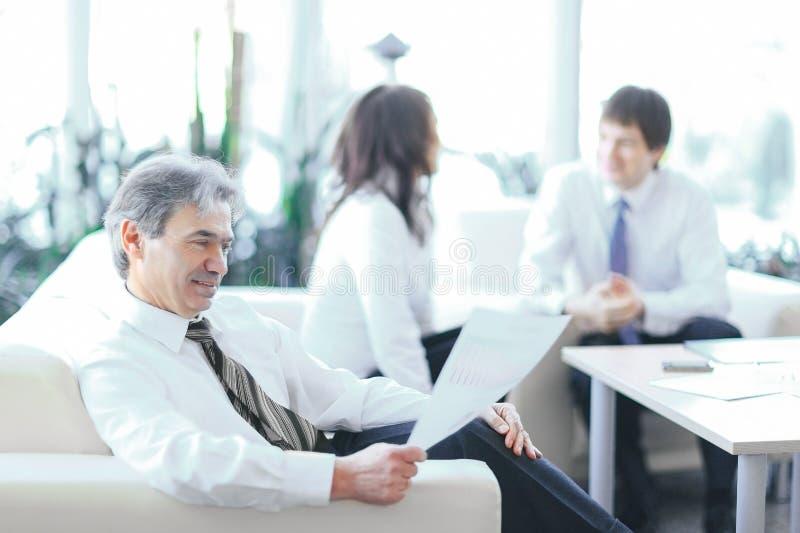 Homme d'affaires consid?rant un document se reposant dans un bureau moderne photos stock