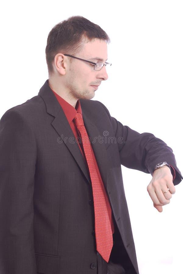 Homme d'affaires contrôlant sa montre-bracelet photographie stock libre de droits