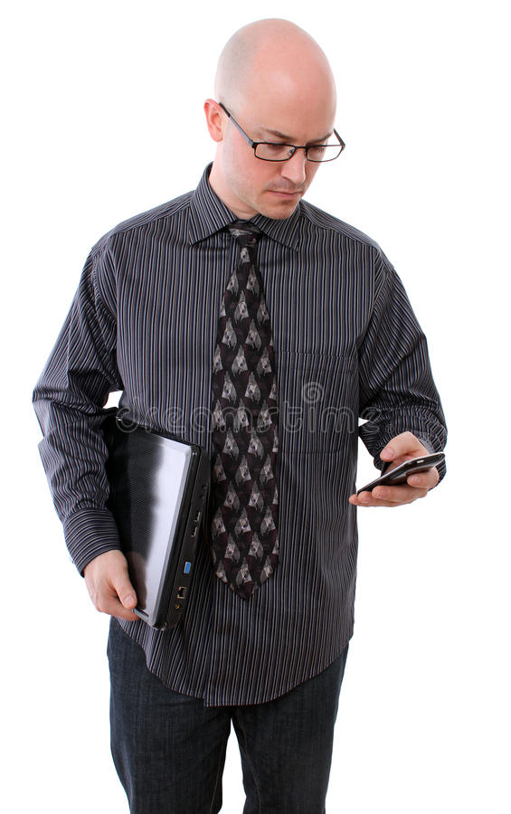 Homme d'affaires contrôlant son téléphone portable et ordinateur portatif photo stock