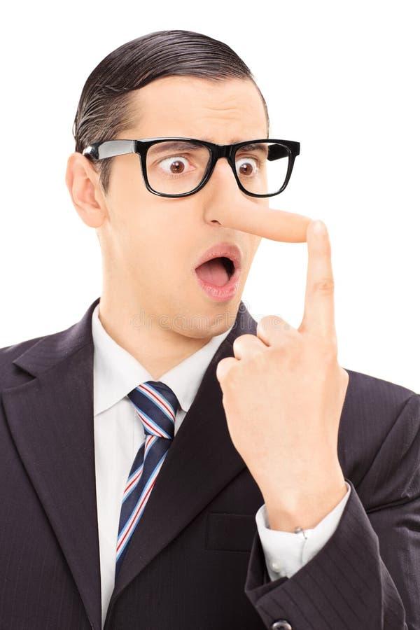 Homme d'affaires contrarié regardant son long nez photos libres de droits