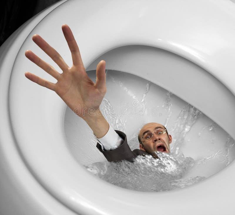 Homme d'affaires coulant dans la cuvette de toilette photographie stock libre de droits
