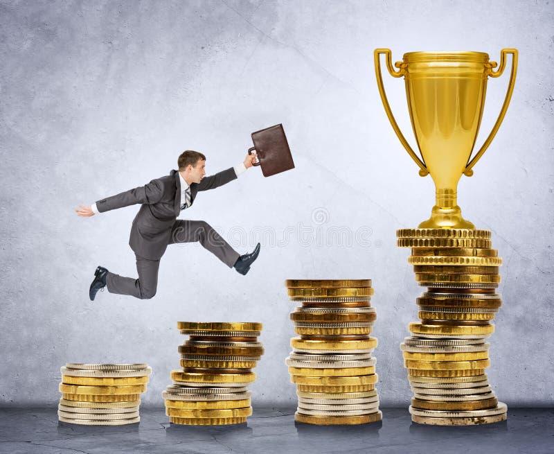 Homme d'affaires courant et sautant sur des escaliers d'argent image stock