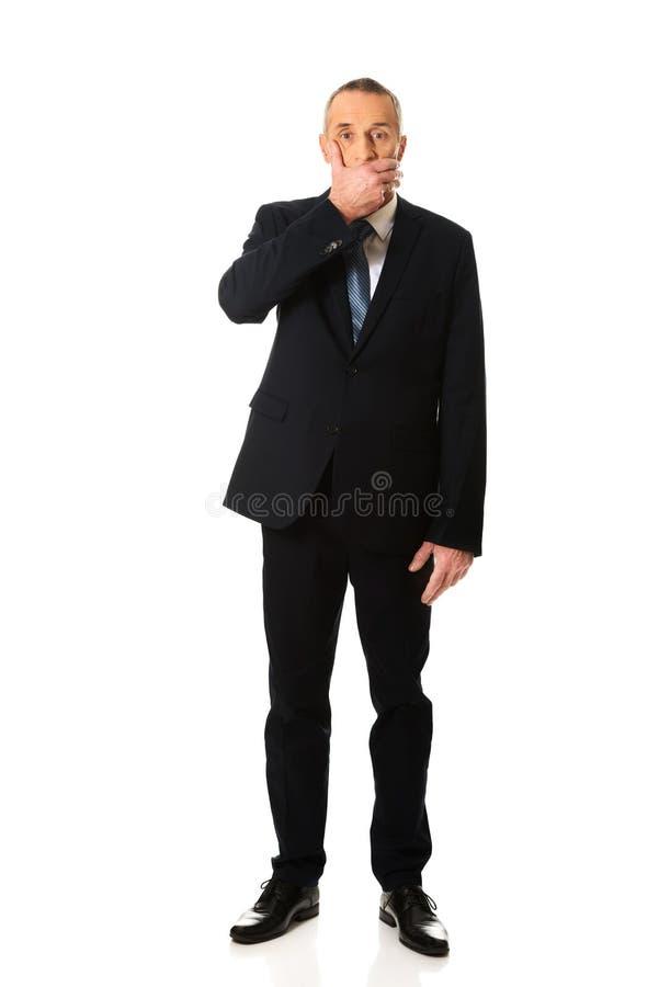 Homme d'affaires couvrant sa bouche images libres de droits
