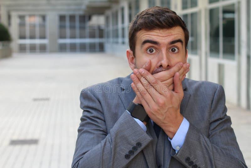 Homme d'affaires couvrant sa bouche après fabrication d'une erreur image libre de droits