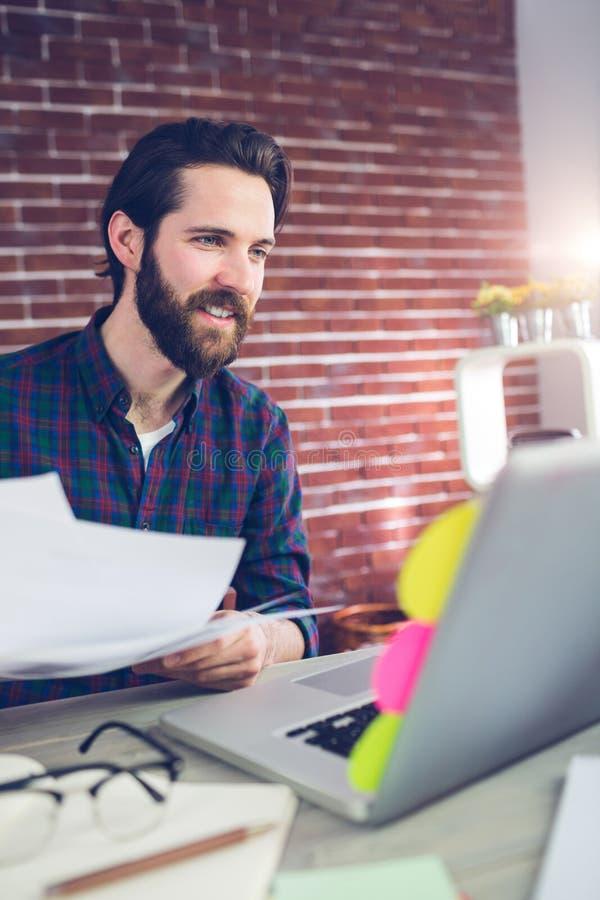 Homme d'affaires créatif de sourire avec des documents utilisant l'ordinateur portable photos stock
