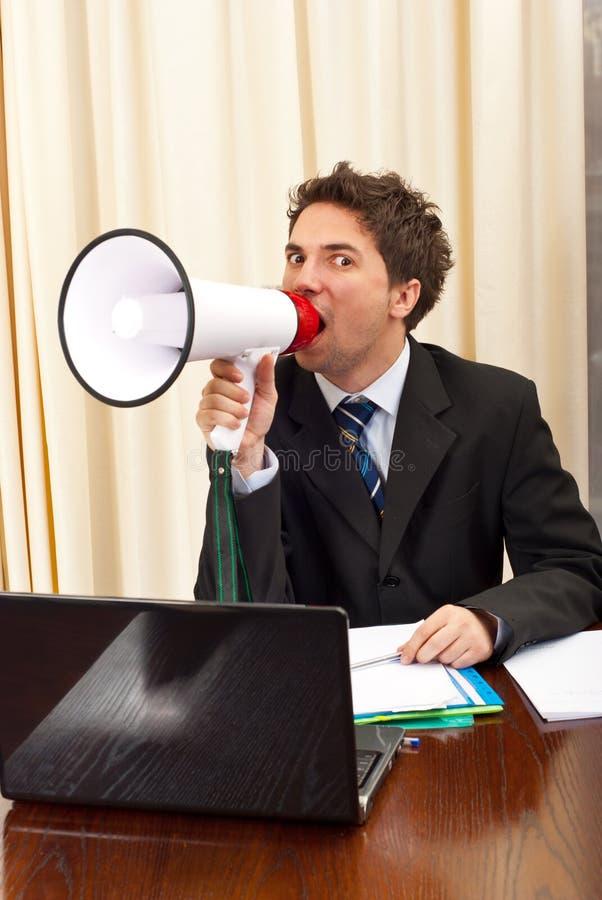 Homme d'affaires criant dans le mégaphone photographie stock