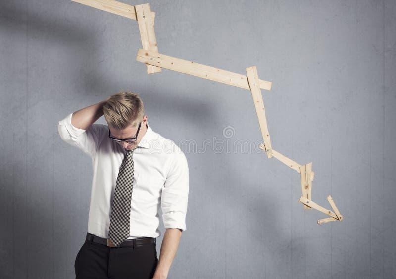 Homme d'affaires déçu devant le graphique se dirigeant vers le bas. image stock
