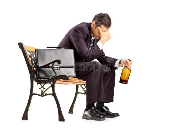 Homme d'affaires déçu s'asseyant sur un banc et tenant une bouteille images libres de droits