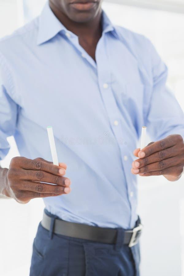 Homme d'affaires décidant entre la cigarette électronique ou normale images libres de droits