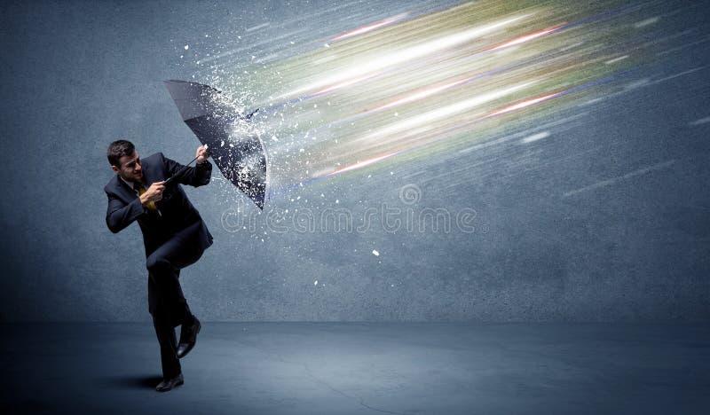 Homme d'affaires défendant les faisceaux lumineux avec le concept de parapluie photo stock