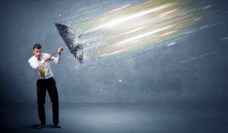 Homme d'affaires défendant les faisceaux lumineux avec le concept de parapluie image stock