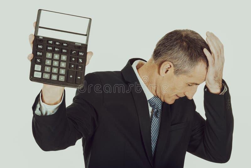 Homme d'affaires déprimé tenant une calculatrice photo stock