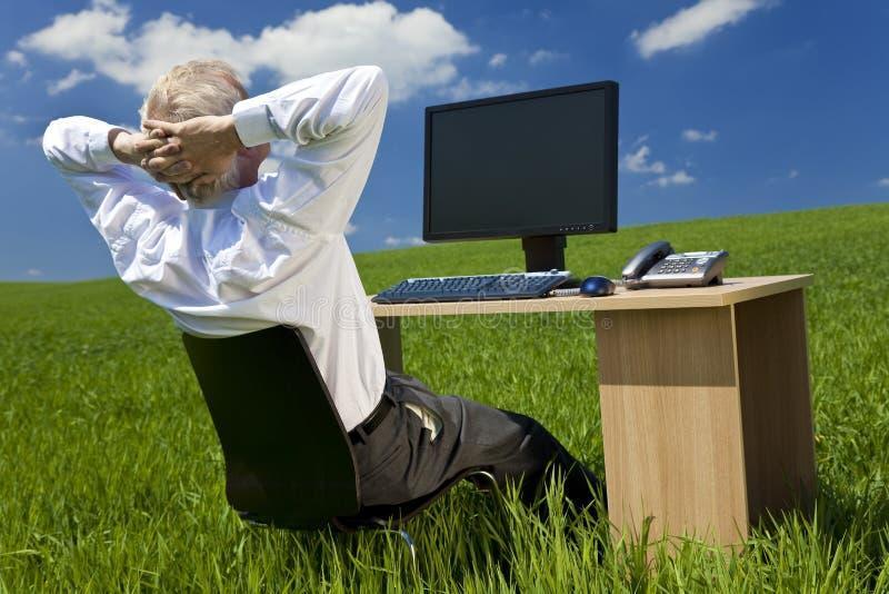 Homme d'affaires détendant au bureau dans le domaine vert image libre de droits