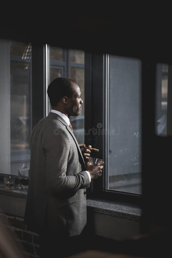 Homme d'affaires d'afro-américain dans le costume avec le verre du cigare de tabagisme de whiskey photo libre de droits