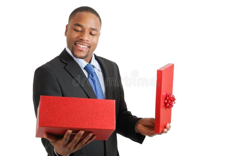 Homme d'affaires d'Afro-américain ouvrant un cadeau photo libre de droits